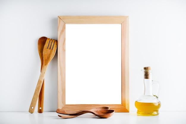 Una cornice di legno vuota e accessori per la cucina su uno sfondo bianco.