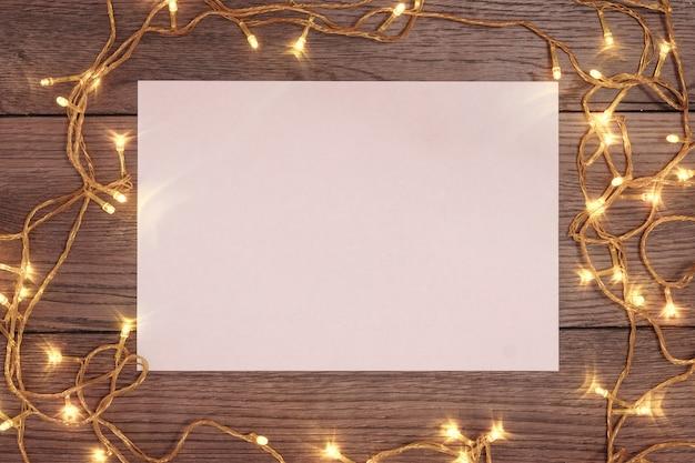 Una cornice di rami di pino e decorazioni natalizie e foglio a4 di carta bianca su un tavolo di legno. vacanze di natale. copyspace. vista dall'alto