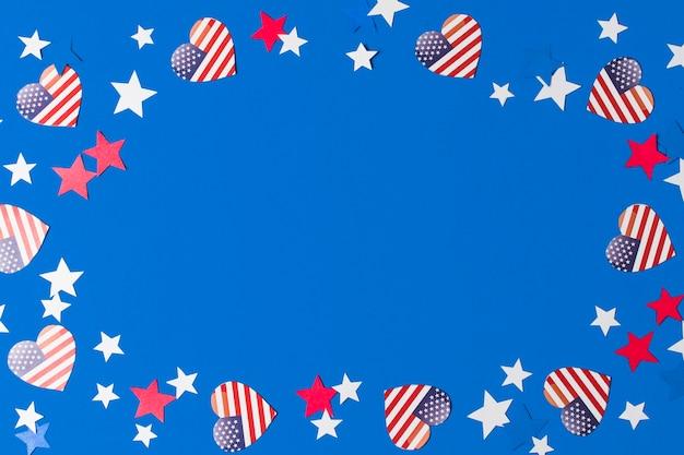 Una cornice fatta con bandiere americane a forma di cuore e stelle per la scrittura del testo su sfondo blu