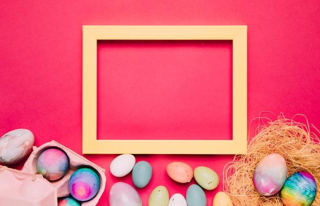 Una cornice gialla vuota con uova di pasqua colorate su sfondo rosa