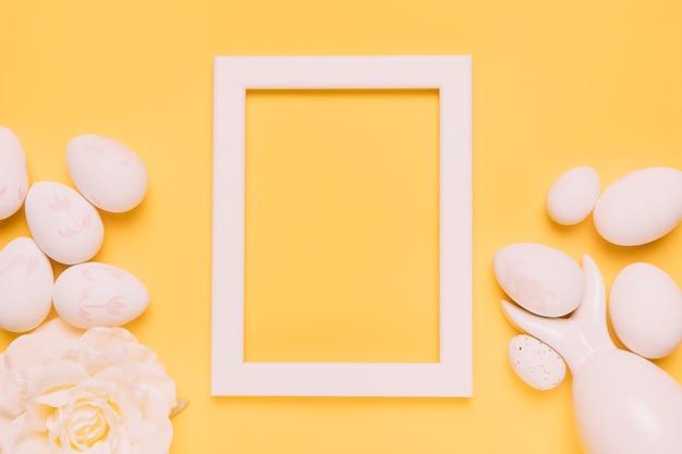 Una cornice vuota bordo bianco con uova di pasqua e rosa su sfondo giallo