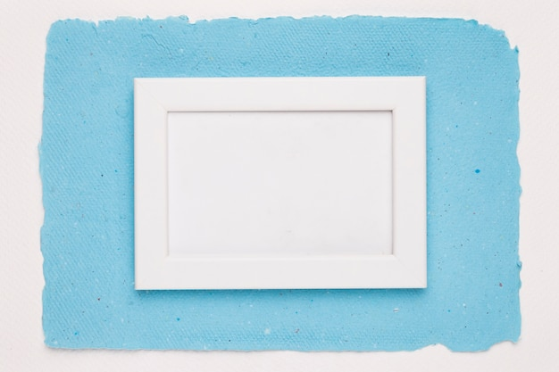 Una cornice vuota bordo bianco su carta blu su sfondo bianco