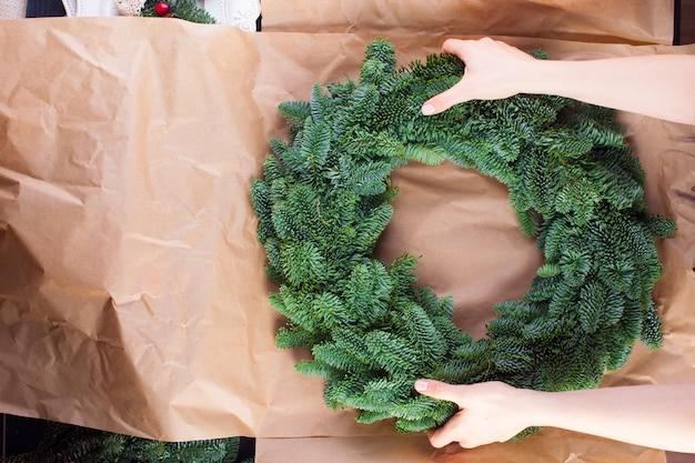 Una corona di alberi di natale in mani femminili e una carta da imballaggio grigia