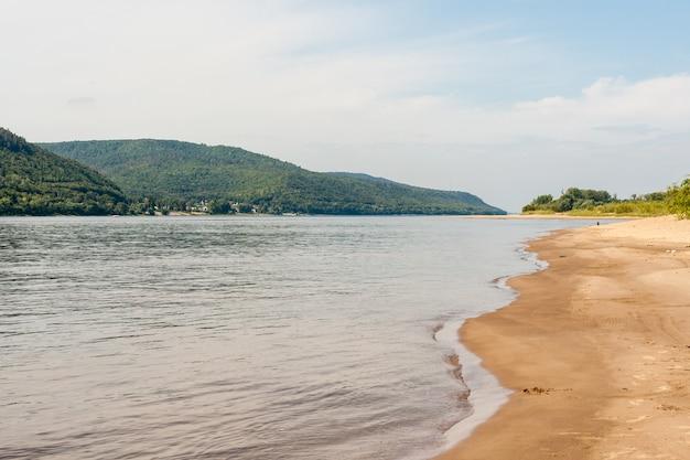 Una costa di sabbia ondulata, verdi montagne boscose di zhiguli e il letto del fiume volga.