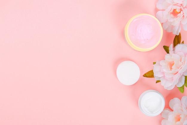 Una crema di cura in un barattolo su uno sfondo pastello con belle peonys. crema anti-invecchiamento.