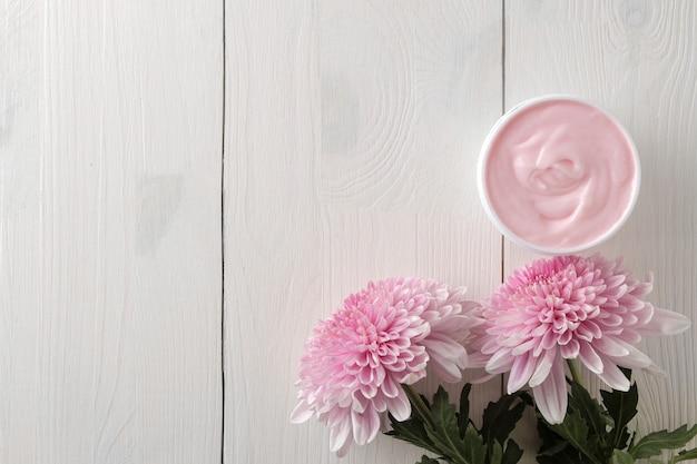 Una crema in un barattolo e fiori di crisantemo su un tavolo di legno bianco con un posto per un'iscrizione.