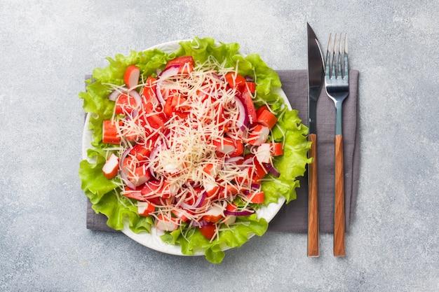 Una deliziosa insalata di granchio attacca i pomodorini e il formaggio grattugiato con le cipolle in un piatto da portata.