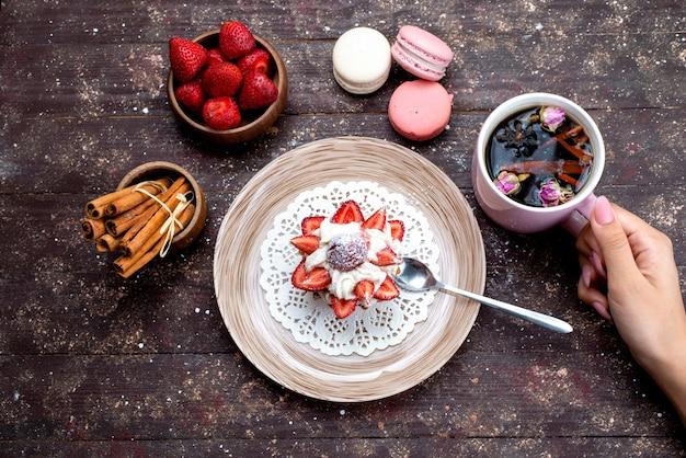 Una deliziosa piccola torta vista dall'alto con panna e frutta fresca a fette insieme a tè alla cannella bevuto da femmine e macarons sulla torta di frutta marrone scrivania