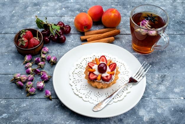 Una deliziosa piccola torta vista dall'alto con panna e frutta fresca a fette insieme a tè alla cannella sul biscotto torta di frutta grigio-blu