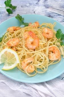 Una deliziosa ricetta per spaghetti con gamberi, decorata con limone e prezzemolo.