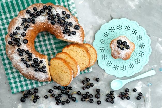 Una deliziosa torta vista dall'alto con mirtilli freschi sullo zucchero bianco della bacca del tè del biscotto della torta della scrivania