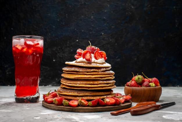 Una deliziosa vista frontale frittelle rotonde con fragole rosse fresche e cocktail alla fragola sulla torta leggera dello scrittorio