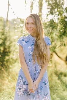 Una dolce e bella giovane donna sorridente in un abito blu con fiori e lunghi capelli biondi.