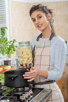 Una donna abbastanza giovane del brunette che cucina nella cucina