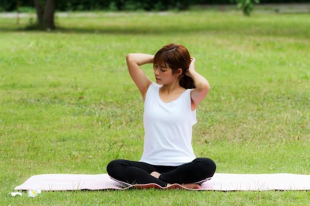 Una donna abbastanza tailandese che si siede su una stuoia e che si riunisce i suoi capelli per praticare yoga nel parco.