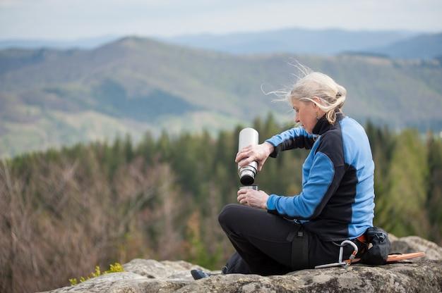 Una donna adulta in giacca blu si siede sulla cima della roccia e versa da un thermos