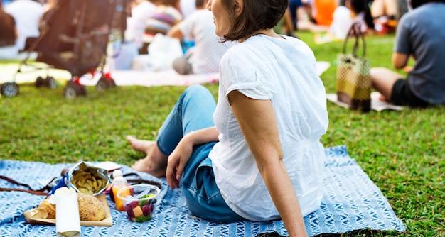 Una donna adulta seduta e pic-nic nel parco
