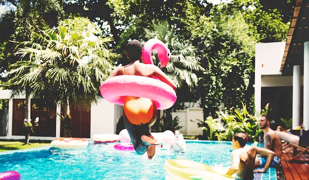Una donna africana che salta nella piscina con galleggianti gonfiabili