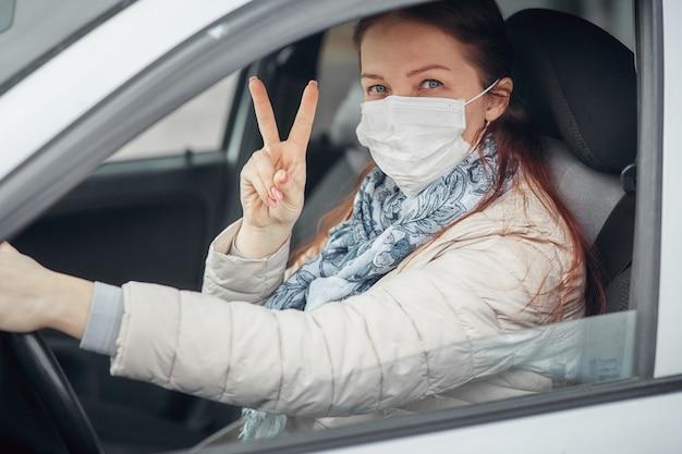 Una donna alla guida di un'auto indossa una mascherina medica durante un'epidemia, un tassista una donna in maschera, protezione dal virus