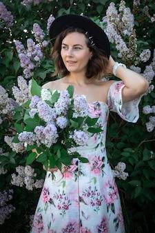 Una donna allegra in un abito leggero con spalle nude e una stampa floreale e un mazzo di lillà