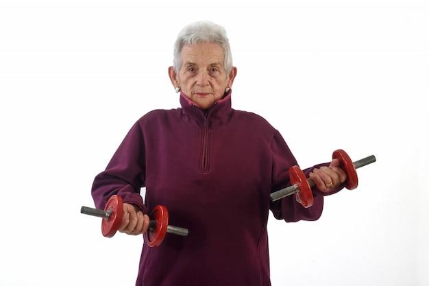 Una donna anziana che fa i dumbbells su priorità bassa bianca