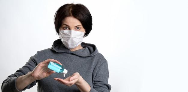 Una donna anziana con una maschera protettiva tiene in sé un gel antibatterico