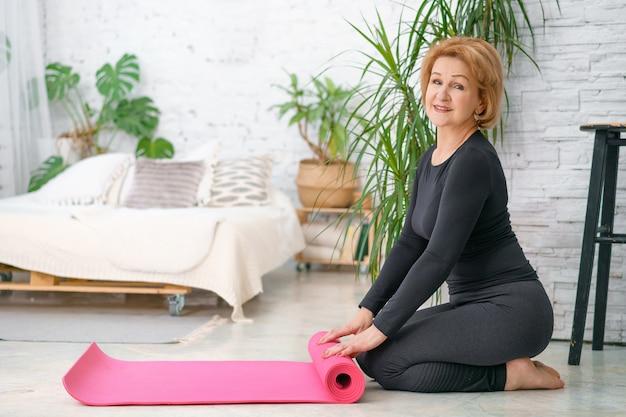 Una donna anziana pone dopo il suo allenamento con un tappetino fitness. concetto di fitness e l'età delle donne.