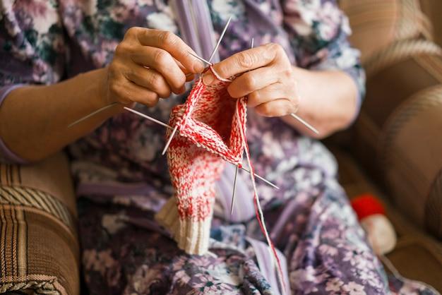 Una donna anziana sta lavorando a maglia dei calzini