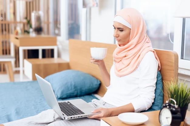 Una donna araba sta bevendo tè e lavora