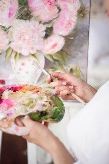 Una donna artista tiene una foto su un cavalletto a casa. il pittore dipinge dipinti ad olio.