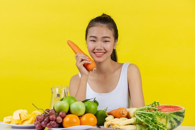 Una donna asiatica che indossa una canotta bianca. tieni le carote con la mano destra e sul tavolo ci sono molti frutti.