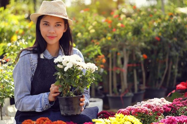 Una donna asiatica che possiede un'azienda di giardini fioriti conta i fiori per soddisfare l'ordine del cliente.