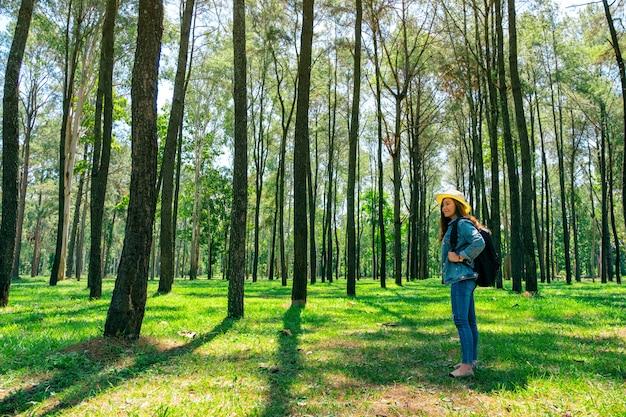 Una donna asiatica che viaggia con un cappello e uno zaino guardando in una bellissima pineta
