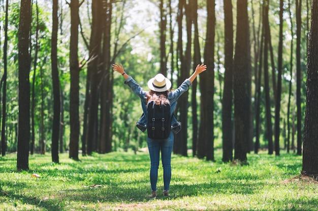 Una donna asiatica che viaggia con un cappello e uno zaino in piedi indietro e a braccia aperte in una splendida pineta