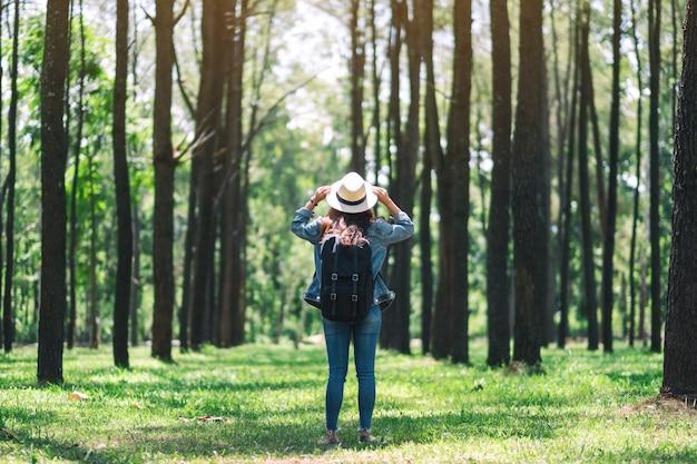 Una donna asiatica che viaggia con un cappello e uno zaino in piedi indietro e guardando in una bellissima pineta