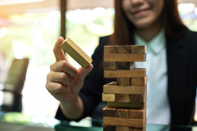 Una donna asiatica costruisce i blocchi di legno della torre di caduta per gestione e strategia nei concetti di affari