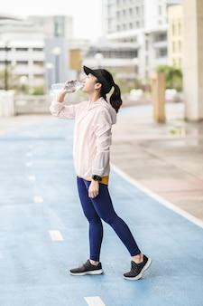Una donna asiatica giovane e attiva che sta bevendo la bottiglia d'acqua