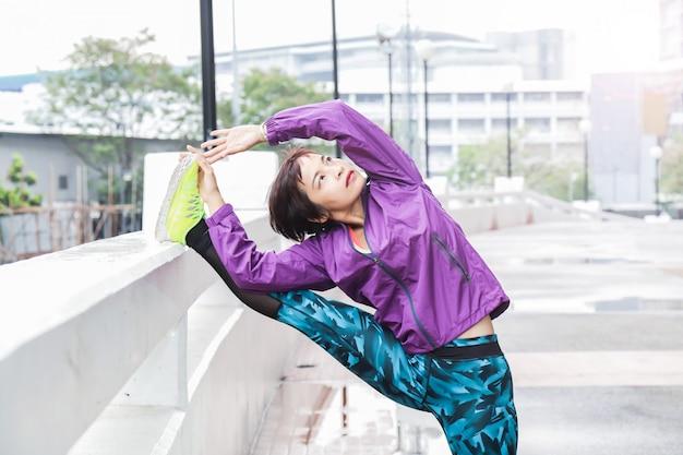 Una donna asiatica giovane e in buona salute sta allungando il suo corpo in un parco pubblico