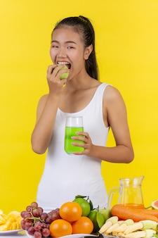 Una donna asiatica sta per mangiare una mela verde. e tieni un bicchiere di succo di mela.
