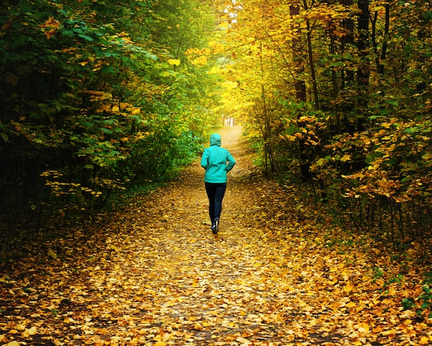 Una donna atleta correre nella foresta d'autunno. fare jogging in una straordinaria foresta autunnale cosparsa di foglie cadute