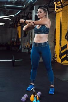 Una donna atletica che allunga le sue mani vicino alle attrezzature di esercizio in palestra