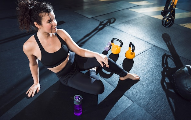 Una donna atletica che si siede vicino alle attrezzature di esercizio in palestra