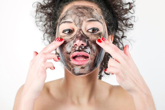 Una donna attraente che applica la maschera di protezione nera con le sue dita contro la priorità bassa bianca