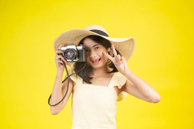 Una donna bella e felice che indossa un grande cappello e una macchina fotografica su un giallo.