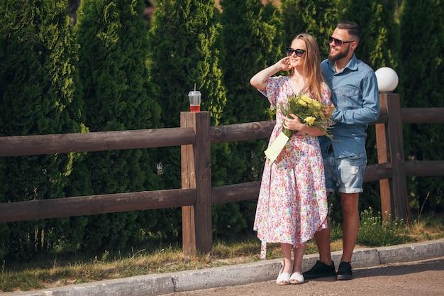 Una donna bella e tenera con i capelli biondi, un vestito leggero e un mazzo di fiori cammina in un parco soleggiato con il suo bel ragazzo in camicia blu e pantaloncini