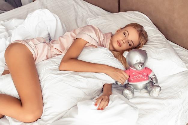Una donna bionda dorme con un orso d'argento a letto