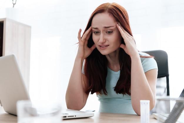 Una donna bruna ha mal di testa. lei si sente male.