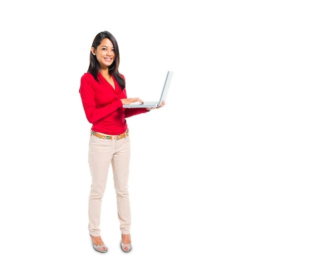 Una donna casuale astuta allegra che per mezzo del suo computer portatile