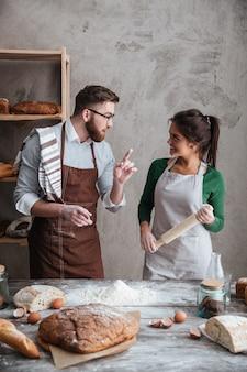 Una donna che ascolta le istruzioni di un uomo sulla cottura del pane