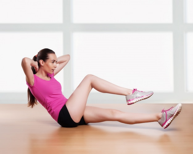 Una donna che esercita sgranocchia le braccia di allenamento fitness dietro la testa